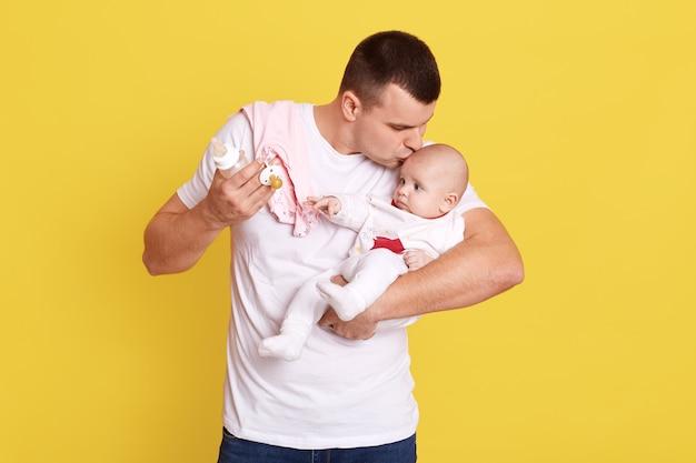 Padre besando a su hija o hijo recién nacido mientras sostiene el biberón y el chupete en las manos