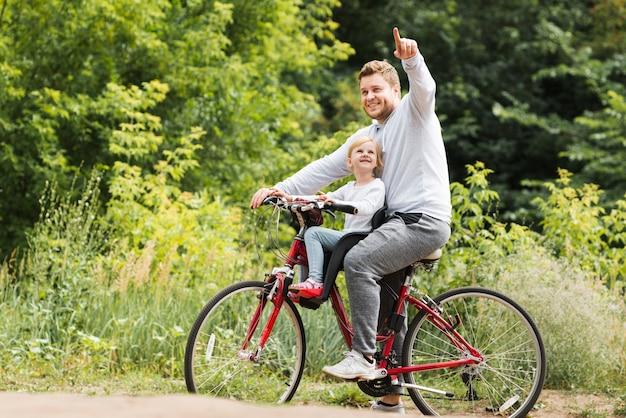 Padre en bicicleta apuntando para hija