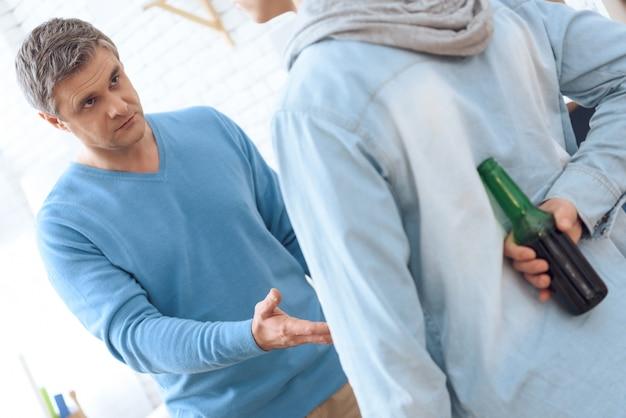Padre borracho enojado pidiendo cerveza a su hijo.