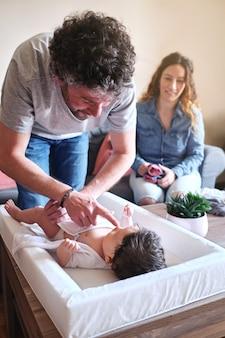 El padre cambia la ropa de su adorable hijita bajo la atenta mirada de la madre