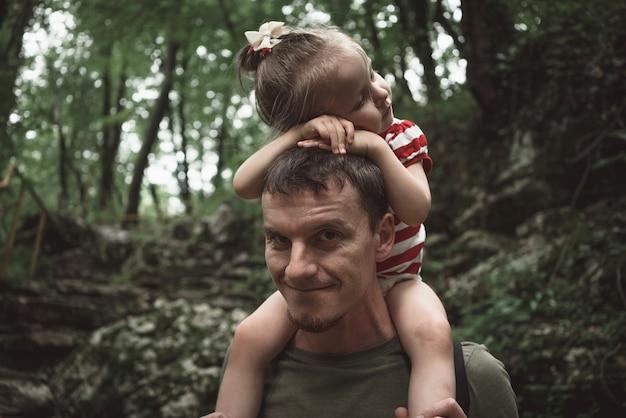 Padre cansado con hija durmiendo en el cuello en el bosque