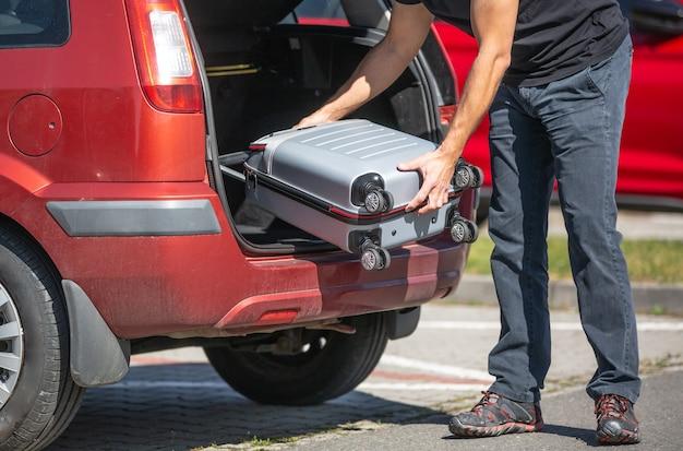 Padre cargando un equipaje en el coche, preparándose para unas vacaciones o vacaciones en el extranjero, concepto de transporte
