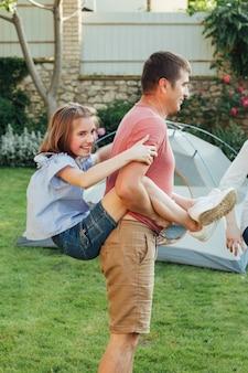 Padre cargando a su hija en el parque