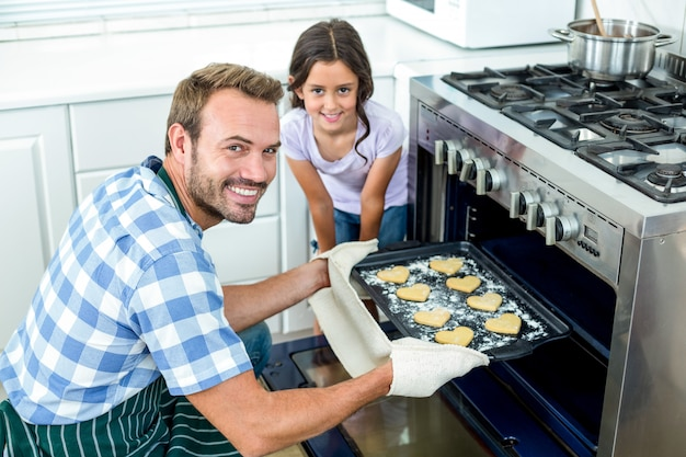Padre colocando la bandeja de galletas en el horno mientras su hija está junto a él