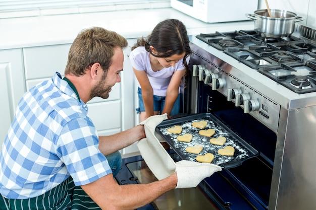 Padre colocando galletas en el horno mientras busca hija