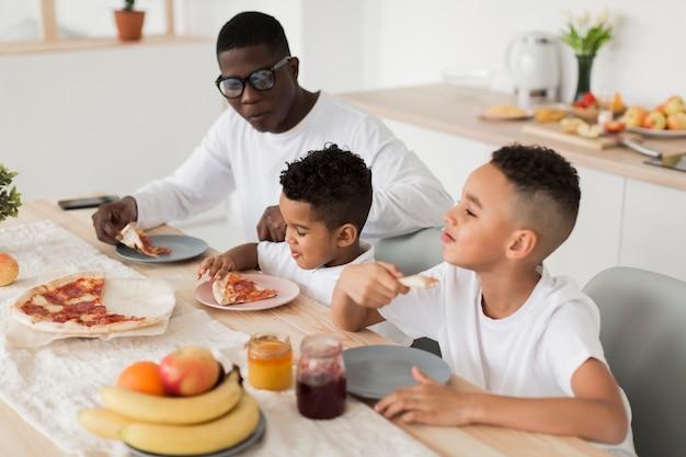 Padre comiendo pizza con sus hijos juntos