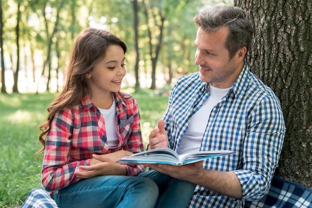 Padre contando la historia a su hija sentada en el parque.