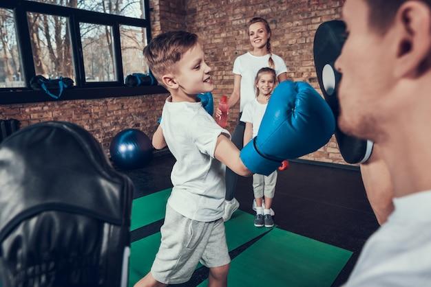 El padre del cuidado entrena al pequeño boxeador en guantes en gimnasio.