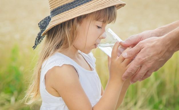 El padre le da agua al niño en el fondo del campo.