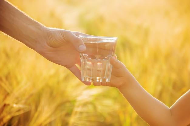 El padre le da al niño un vaso de agua. enfoque selectivo