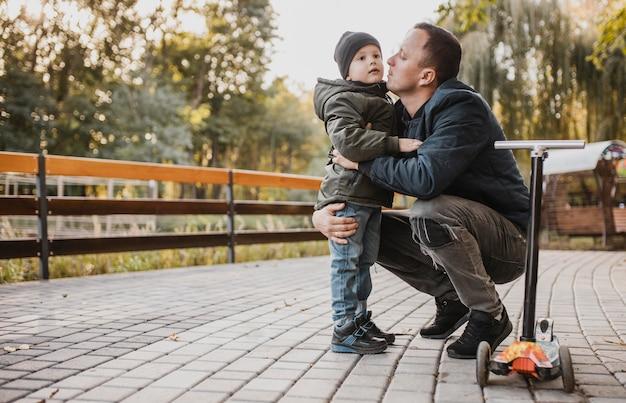 Padre le está dando un beso a su hijo