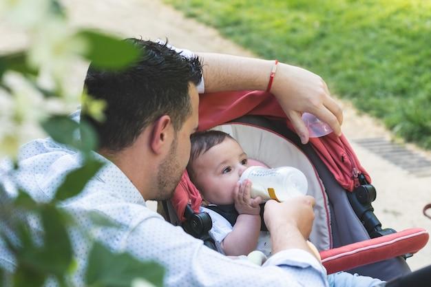 Padre divorciado alimentando a su hijo bebé al aire libre.