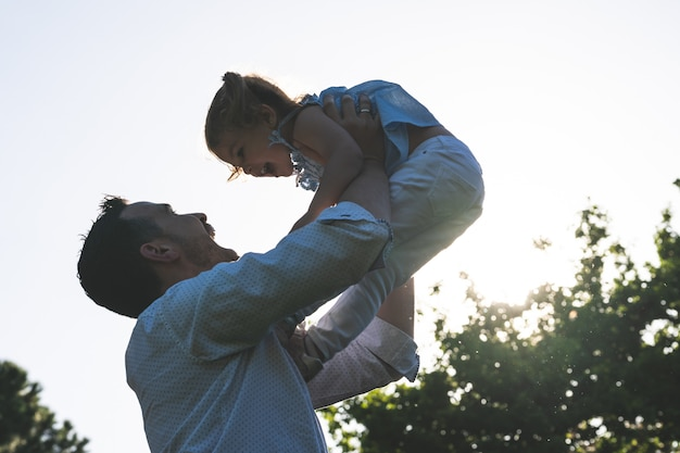 Padre divorciado jugando con su hija al aire libre.