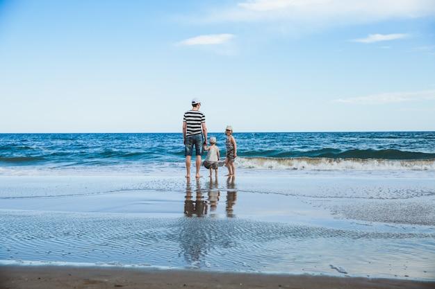 Padre y dos hijas de pie en la playa, mar mediterráneo