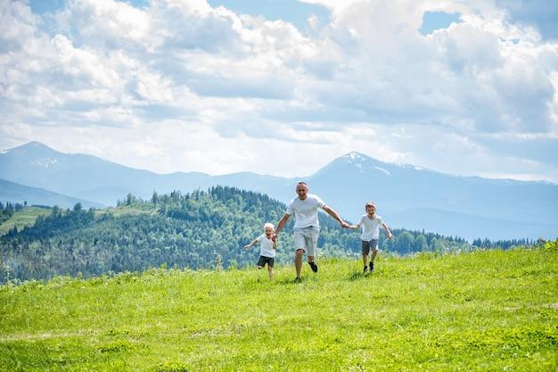 Padre y dos hijos pequeños corriendo en el campo verde cogidos de la mano