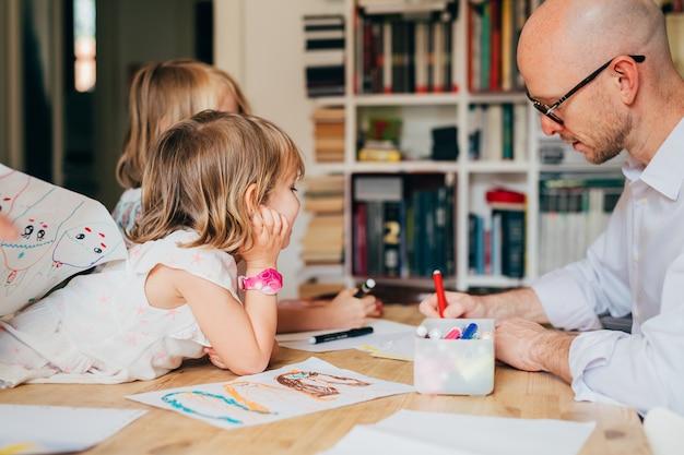 Padre de dos niñas dibujando en un papel interior en casa
