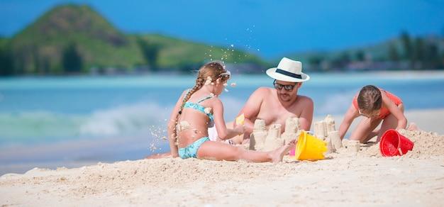 Padre y dos niñas jugando con arena en playa tropical