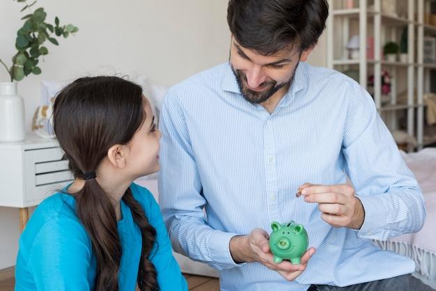 Padre e hija con alcancía