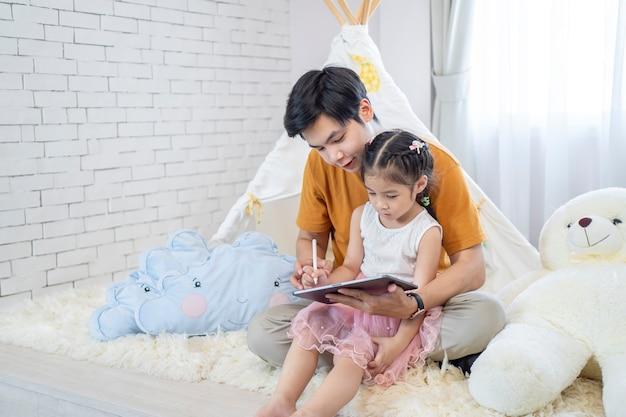 Padre e hija, aprender y jugar con la computadora portátil en casa