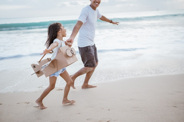 Padre e hija asiáticos corriendo en la playa juegan con avión de juguete de cartón