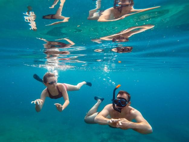 Padre e hija buceando en el mar