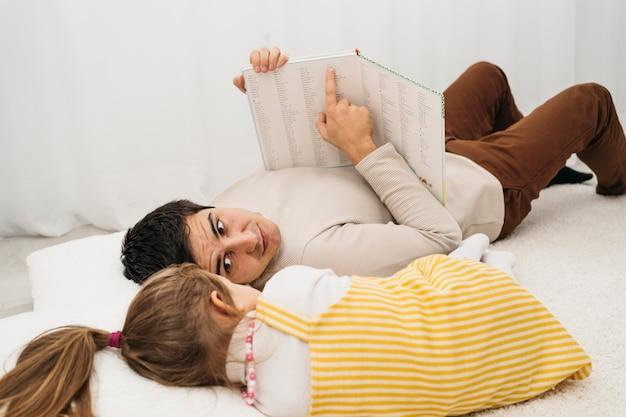 Padre e hija en la cama en casa pasar tiempo juntos