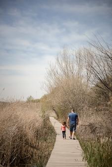 Padre e hija caminando en un camino de tablas de madera en un humedal, granada, andalucía