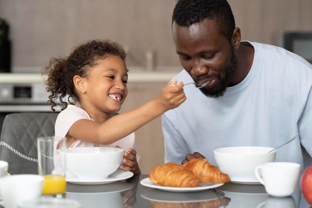 Padre e hija comiendo en la cocina