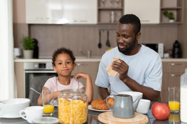 Padre e hija comiendo juntos