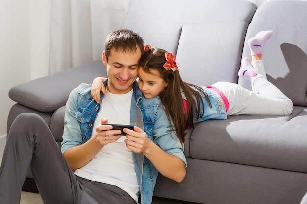 Padre e hija compartiendo algo gracioso en un teléfono móvil
