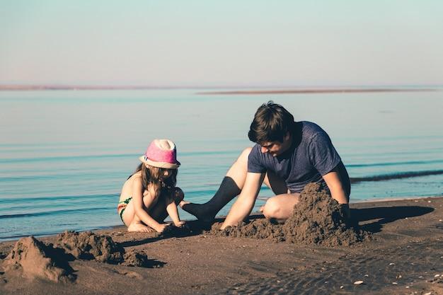 Padre e hija construyen castillos de arena en la playa. foto de estilo de vida tonificada.