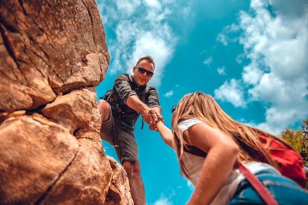 Padre e hija escalando en acantilado