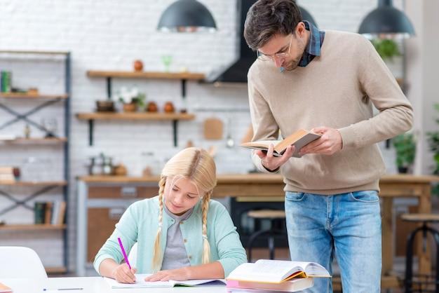 Padre e hija, estudiar en la cocina