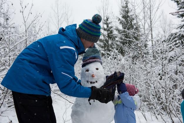 Padre e hija haciendo muñeco de nieve