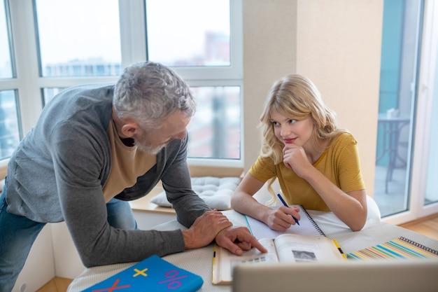 Padre e hija. un hombre canoso de pie junto a su hija mientras ella trabaja en la computadora portátil