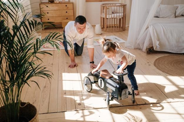 Padre e hija juegan y juegan en la habitación de los niños en casa con un coche retro. interior elegante