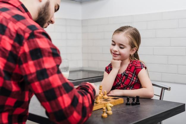 Padre e hija jugando al ajedrez en el día del padre