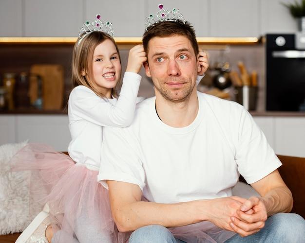 Padre e hija jugando con tiara juntos