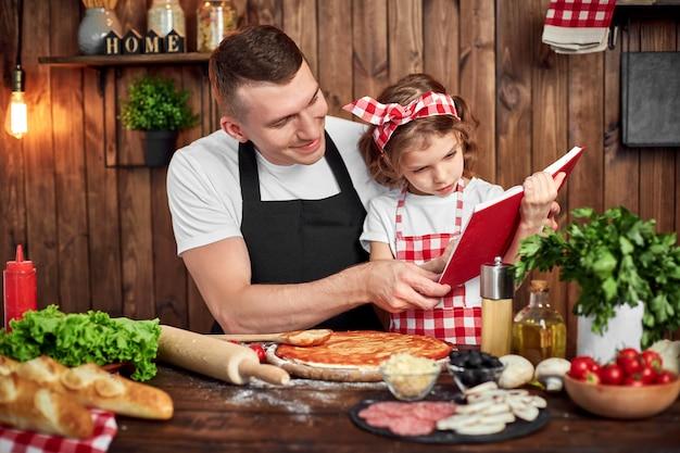 Padre e hija leyendo el libro de recetas mientras cocina pizza