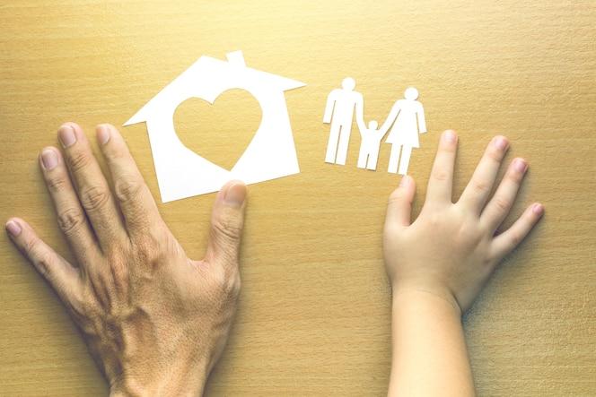 Padre e hija manos con pequeño modelo de casa y familia sobre fondo de madera