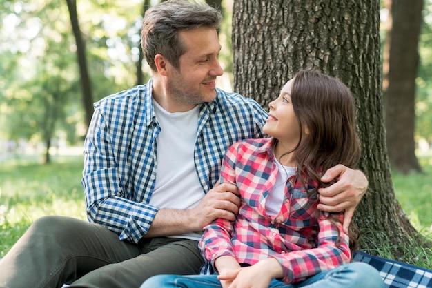 Padre e hija mirándose sentados cerca de un árbol