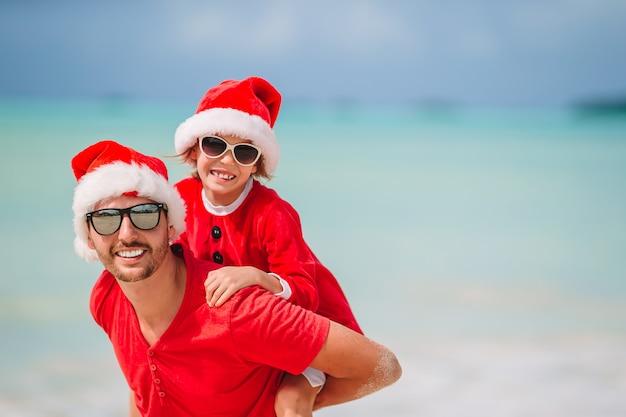 Padre e hija en santa hat se divierten en playa tropical