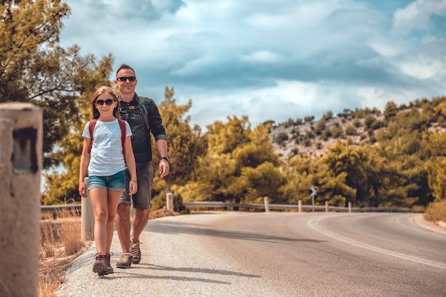 Padre e hija, senderismo en la carretera de montaña