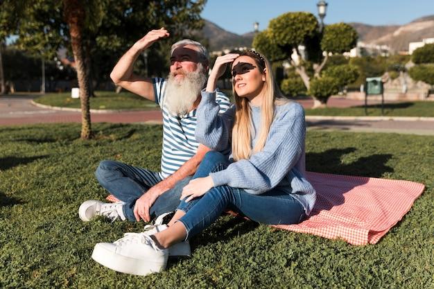 Padre e hija sentada sobre una manta
