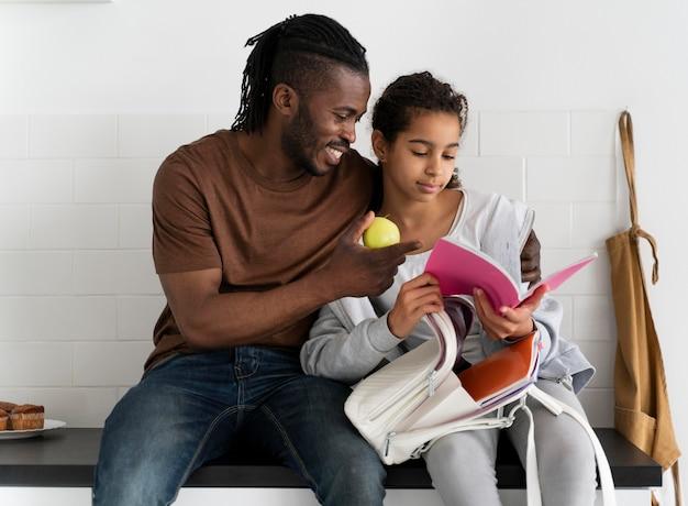 Padre e hija sentados en una encimera de cocina