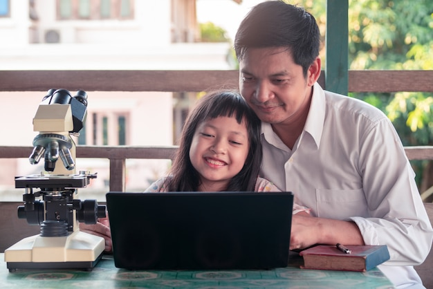 Padre e hija sonriendo y aprendiendo desde casa con una computadora portátil y un microscopio