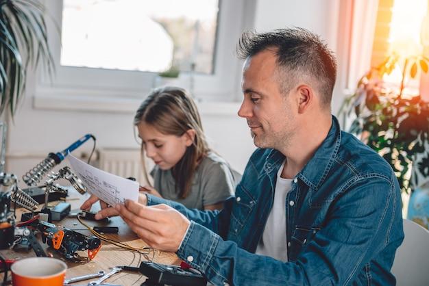 Padre e hija trabajando en componentes electrónicos.