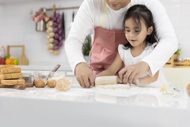 Padre e hija usando un rodillo en la cocina en casa