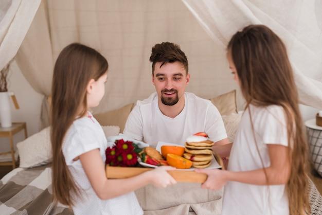 Padre e hijas desayunando en el día del padre