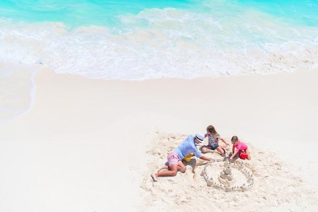 Padre e hijas haciendo castillos de arena en playa tropical